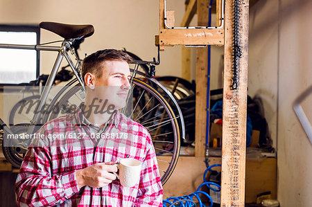 Thoughtful repairman holding coffee mug while looking away at workshop