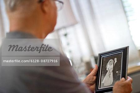 Senior man looking at an old wedding photo.
