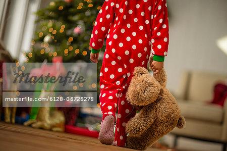 Young girl carrying her teddy bear towards the Christmas tree on Christmas morning.