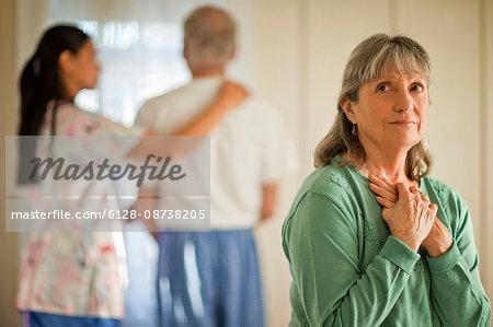 Senior woman looking hopeful while a nurse comforts her unwell husband.