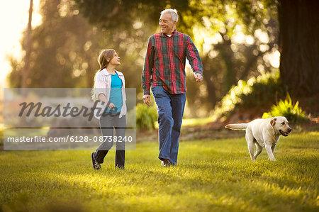 Smiling senior man bonding with his young granddaughter and golden labrador.