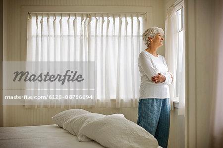 Elderly woman looking through bedroom window.
