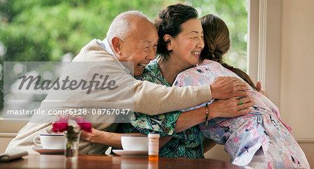Excited senior couple hugging a female nurse.