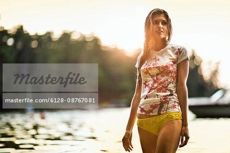 Beautiful young woman wearing a yellow bikini bottom and t shirt in a lake.