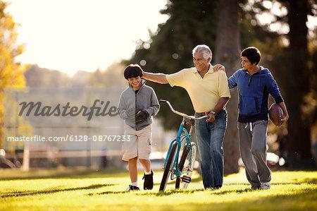 Smiling senior man having fun walking with his two grandsons through a park while wheeling a bicycle.