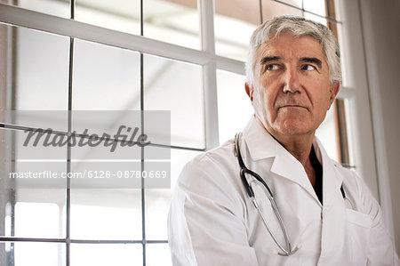 Portrait of worried looking doctor sitting in corridor.