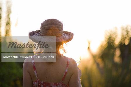 Woman sitting outside at sunset.