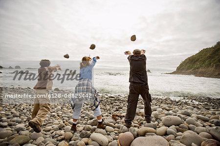 Mature man with his teenage grandchildren throwing rocks into the sea.