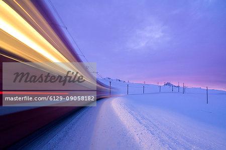 Bernina Express train runs fast in the snowy landscape at dawn Bernina Pass Canton of Graubünden Engadine Switzerland Europe
