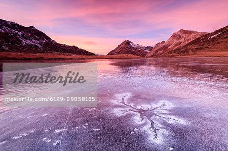 Pink sky at sunset frames the frozen surface of Lej Nair Bernina Pass Canton of Graubünden Engadine Switzerland Europe