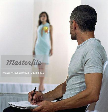 Mature man taking notes while watching fashion show (focus on man)