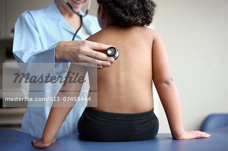 Doctor listens to girl's breathing.