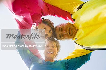 Three adults embracing