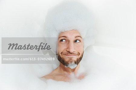 Portrait of man in bath tub, foam on head