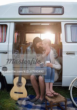 Couple together in camper van embracing.