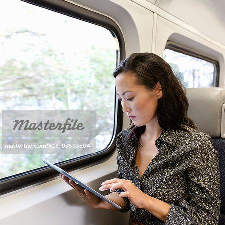 Woman on train using digital tablet