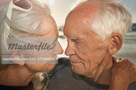 Mature couple embracing at sunset, close up