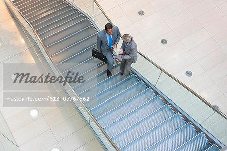 Business people using digital tablet in lobby