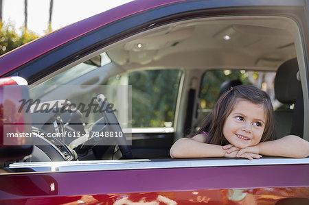 Smiling girl looking out open window of minivan
