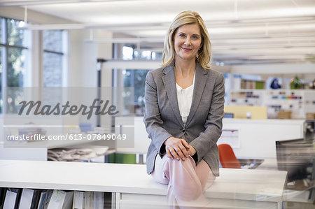 Portrait of confident mature businesswoman sitting on desk