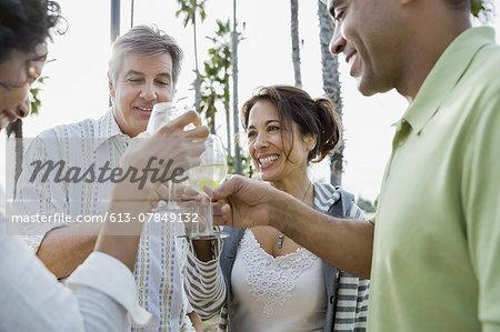 Smiling friends enjoying drinks on patio at resort