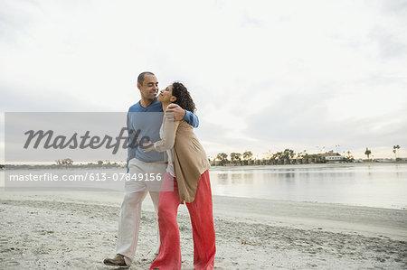 Romantic mature couple walking on beach