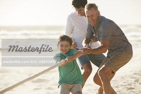 Family playing tug of war on beach