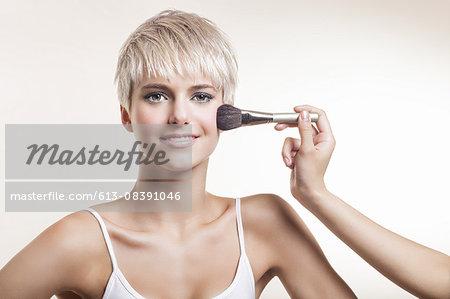 Lady with short blonde hair, having blush on cheek
