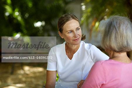 Caretaker with senior woman in park