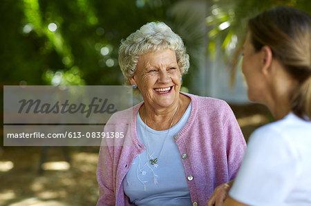Cheerful senior woman looking at caretaker