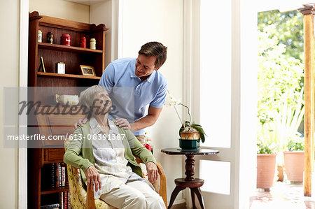 Male caretaker consoling senior woman