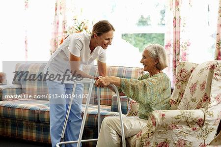 Caretaker assisting senior woman with walker