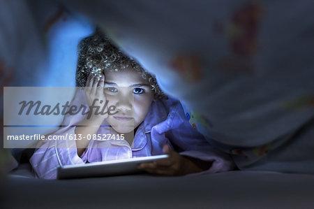 Girl using digital tablet under blanket in bed