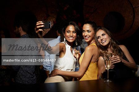 Happy women taking self portrait at nightclub