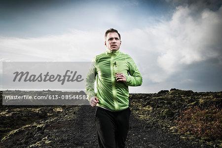 Determined man running on arid landscape