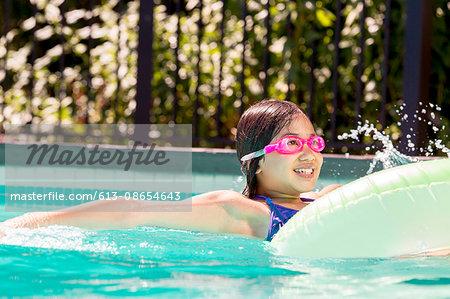 Smiling girl floating in inner tube in pool