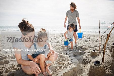 Family building sandcastle on beach