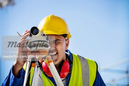 Architect examining site through theodolite