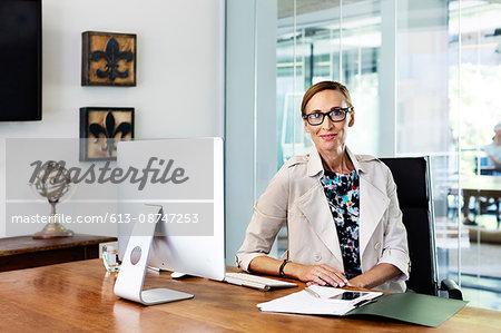 Confident businesswoman sitting at computer desk