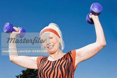 Senior adult woman lifting dumbbells