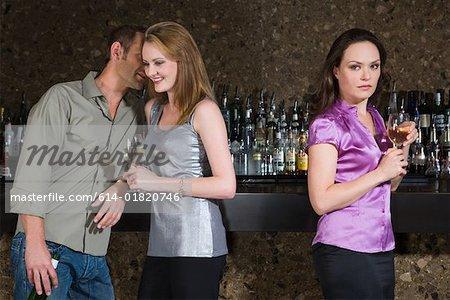 Jealous woman near flirting couple