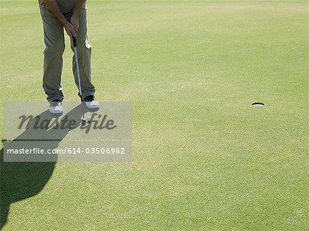 Man playing golf, on putting green