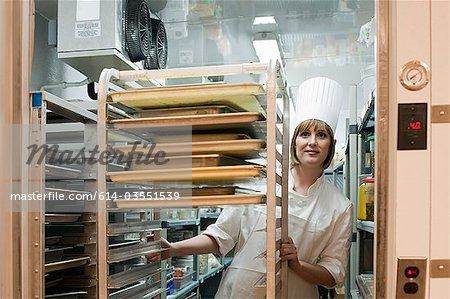 Female chef in walk in freezer in commercial kitchen