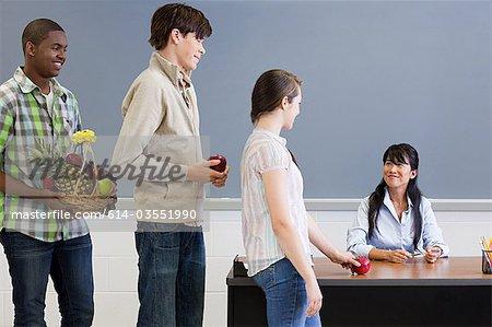 High school student giving teacher an apple