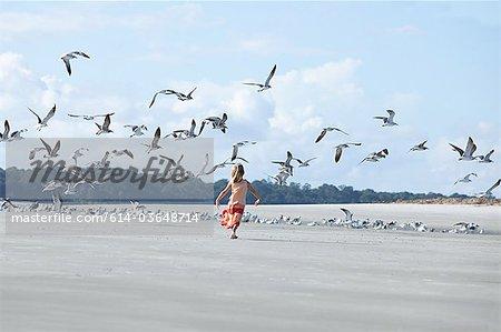 Girl running on beach amongst seagulls