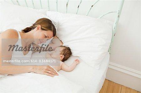 Mother watching baby girl sleep