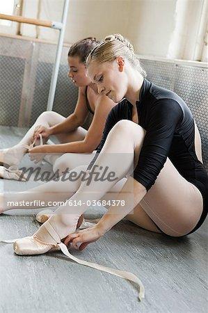Ballerinas putting on ballet slippers