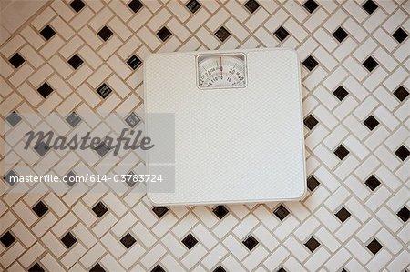 Bathroom scales on tiled floor