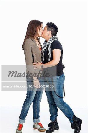 Lesbian couple kissing against white background
