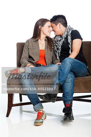 Lesbian couple on sofa against white background